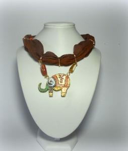 ANISA, cod. LML C08 collarino foulard in cotone indiano sui toni del marrone. Pendente elefante in legno decorato con strass di vari colori. Corniloine cilindriche fungono da connettori.REPLICABILE E PERSONALIZZABILE