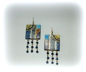 BABAR, COD LML OR 05 orecchini formati da un quadrato in legno dipinto a mano con dettagli argento e oro ricco. Ben 18 mezzi cristalli blu notte impreziosiscono il tutto.REPLICABILE E PERSONALIZZABILE