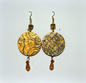 MAIA: COD LML OR 16 orecchini a cerchio da 3,5 cm decorati a mano con diverse gradazione di oro. Rilievi in oro e in glitter oro. Piccole gocce in swaroski pendono come terminali. Monachelle oro senza nichel. REPLICABILE E PERSONALIZZABILE